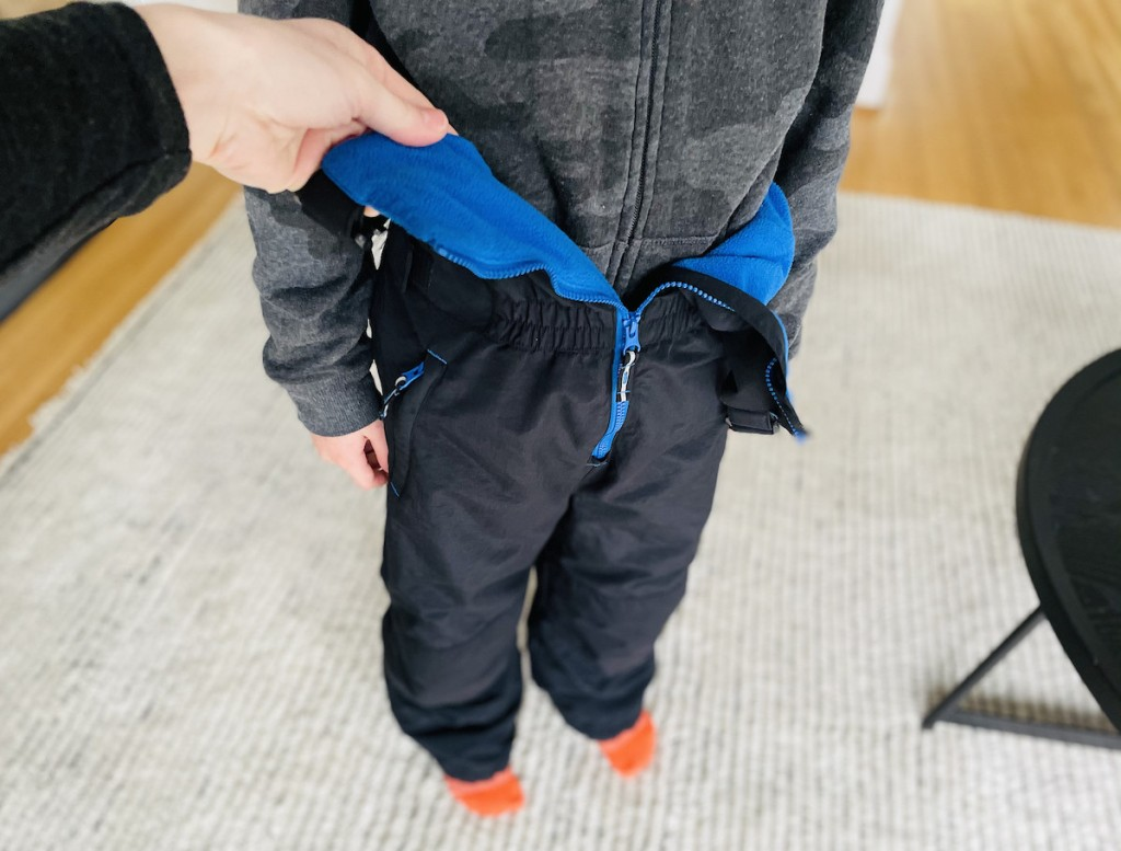 hand holding open a pair of black and blue kids snowpants