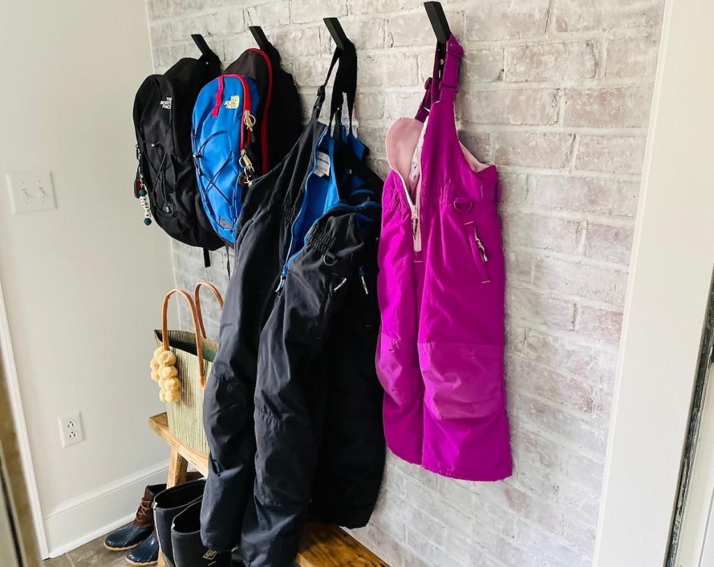 black and purple kids snow pants hanging in mudroom on brick wall