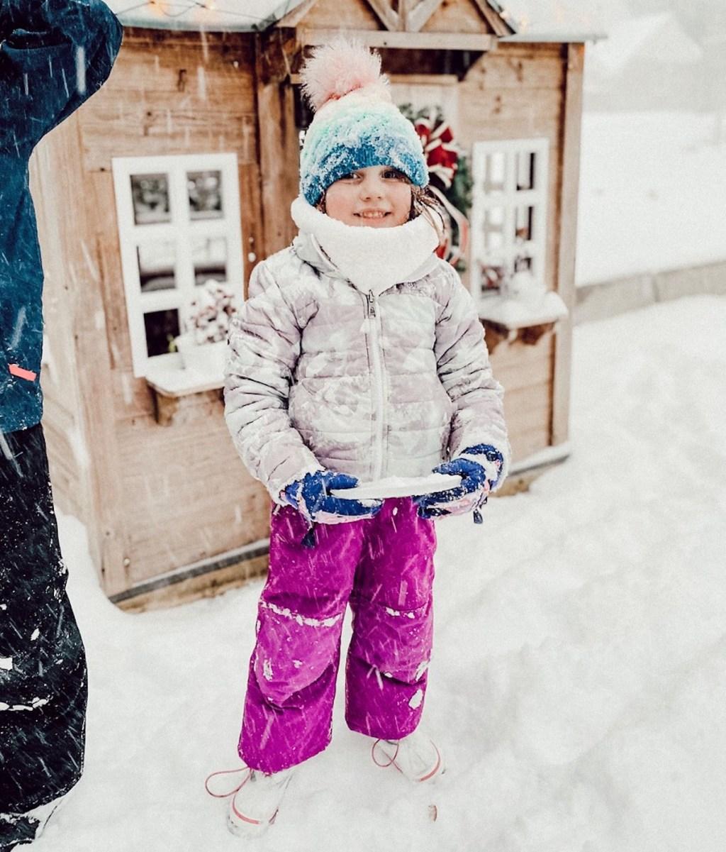 girl wearing winter gear outside in snow