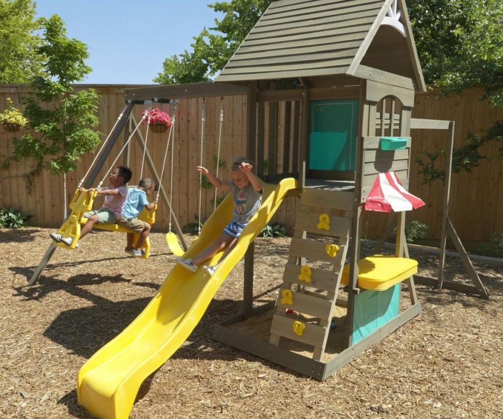 kidskraft hampton swingset with kids playing in backyard