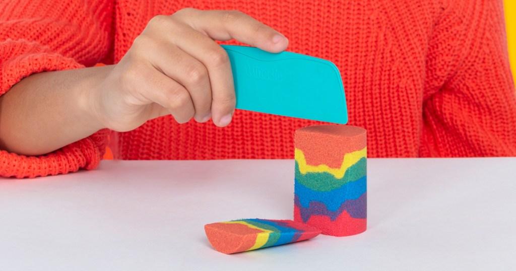 girl cutting kinetic sand rainbow
