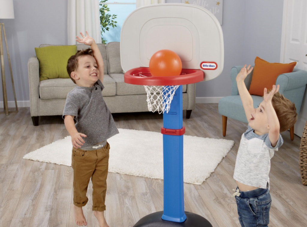 two kids playing on little tikes basketball hoop in living room