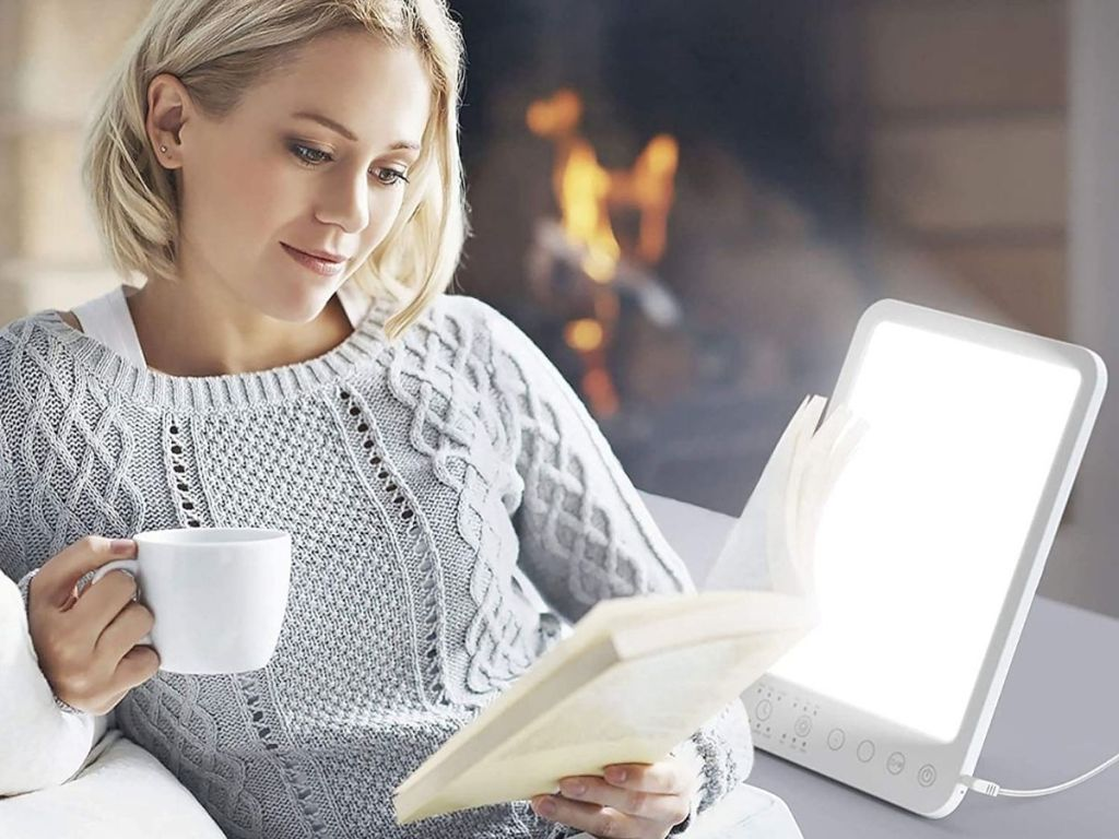 woman drinking coffee, reading and sitting next to light therapy lamp