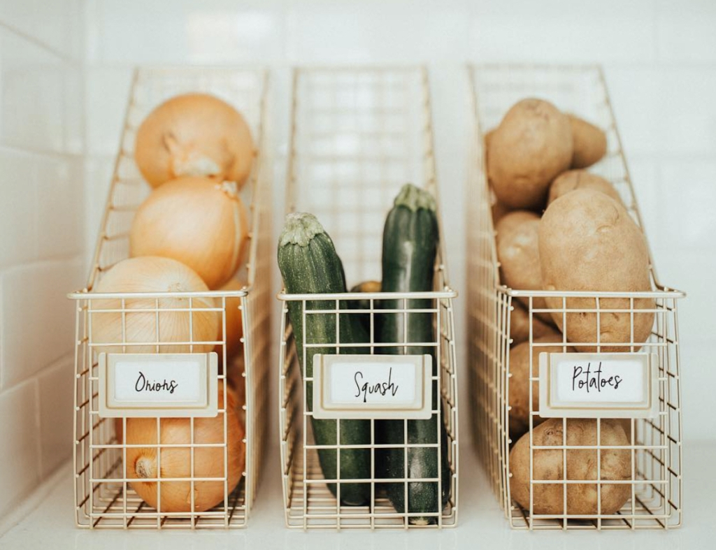 row of onions squash and potatoes on shelf in labeled wire magazine holders