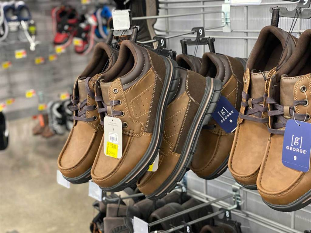 men's boots hanging up on display in store
