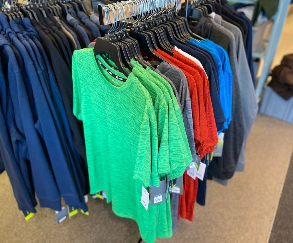 colorful short sleeve workout shirts hanging on store rack