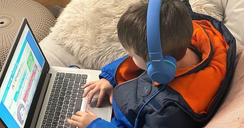 boy wearing blue headphones playing on laptop