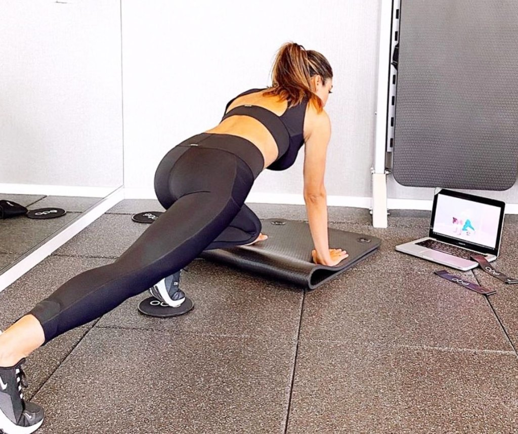 woman working out on floor in front of laptop