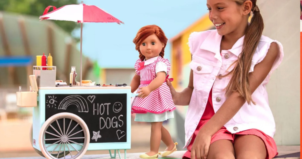 girl playing with our generation doll and hot dog cart