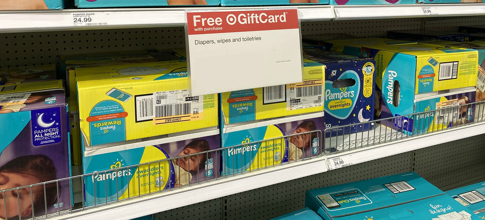 boxes of pampers overnight diapers on a target store shelf near promotional signage