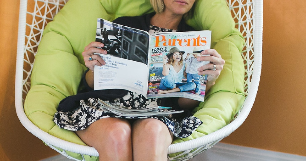 woman holding magazine in egg chair