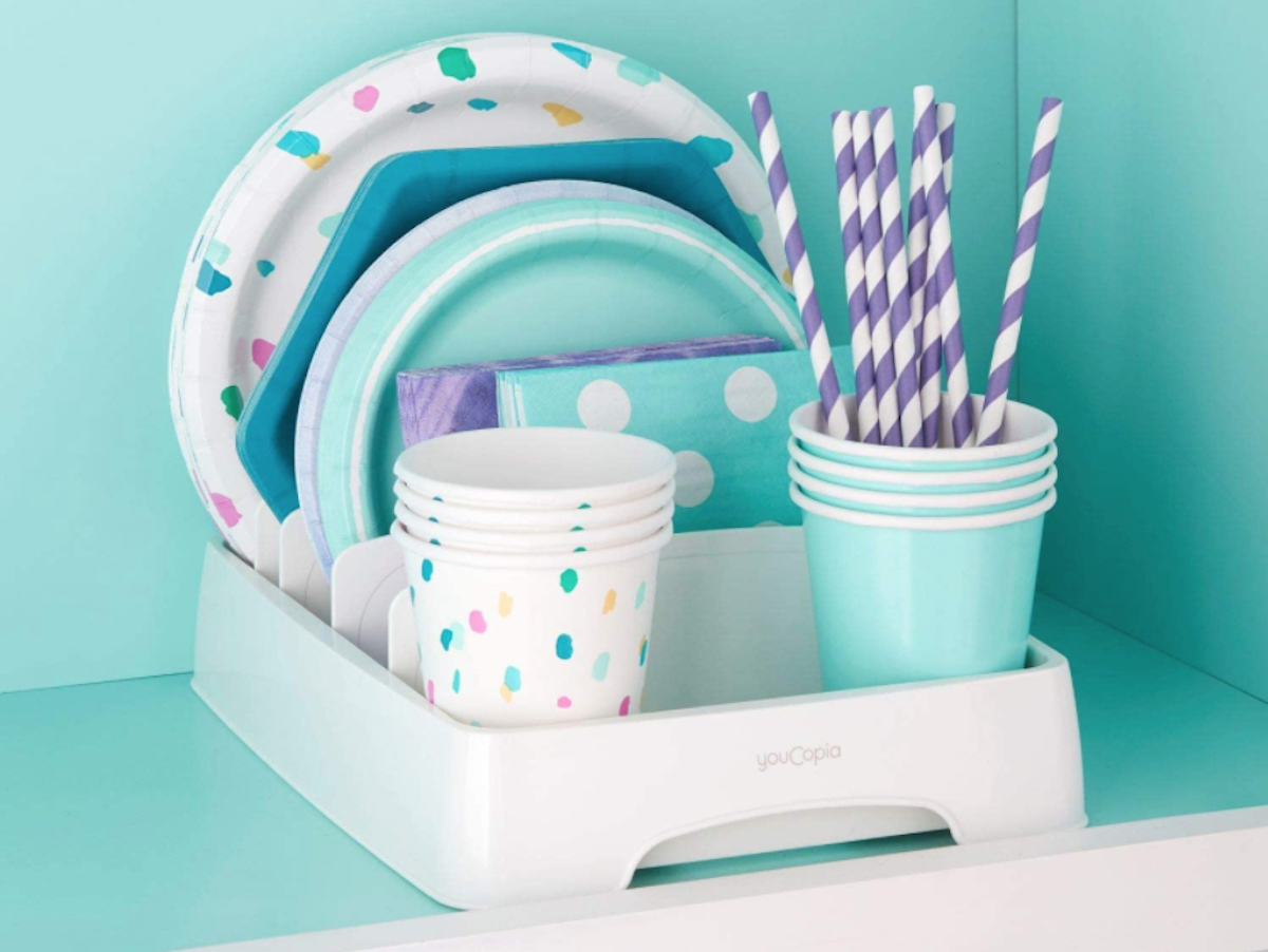 colorful party supplies in organizer on shelf with bright blue wall