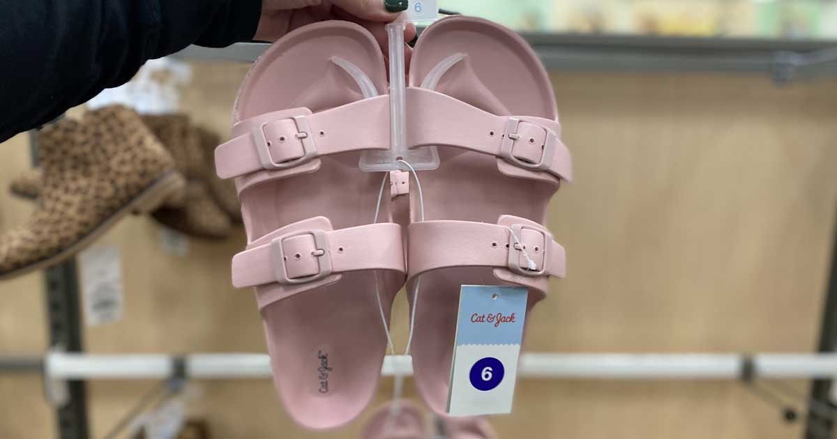 hand holding a pair of birkenstock like sandals pink in store