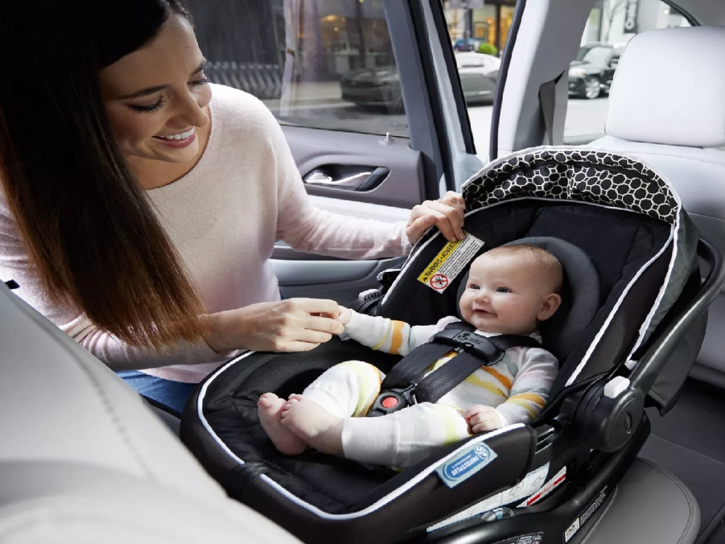 baby in car seat with mom nearby