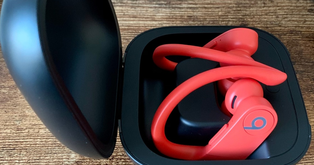Pair of lava red wireless beats in black case on wooden table