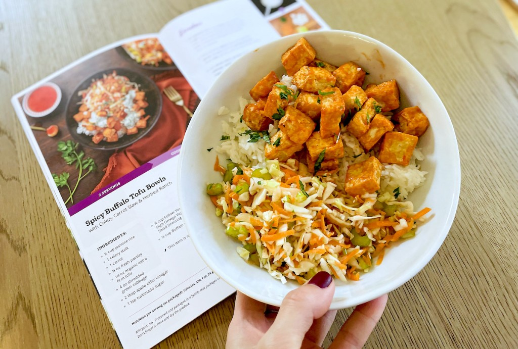 hand holding bowl of buffalo tofu from vegan meal kit