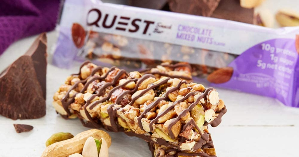 quest bar, chocolate with mixed nuts out of the package with a few nuts beside it and one in the package behind it