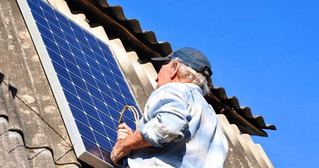 man on a roof with solar panel