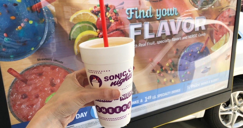 sonic drive in slush in hand in front of sign