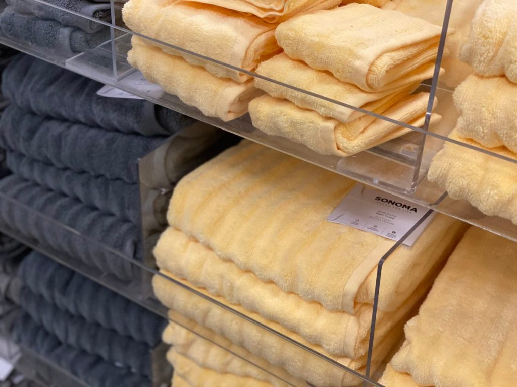 stacks of blue gray and yellow towels on clear shelves