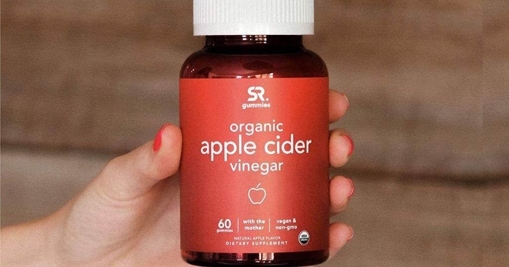 hand holding organic apple cider vinegar bottle