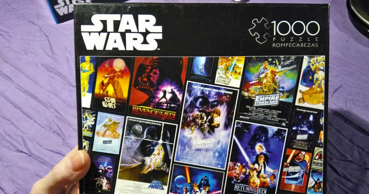 hand holding a star wars jigsaw puzzle box