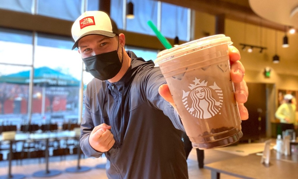 man holding starbucks cookies and cream cold brew drink with mask on his face