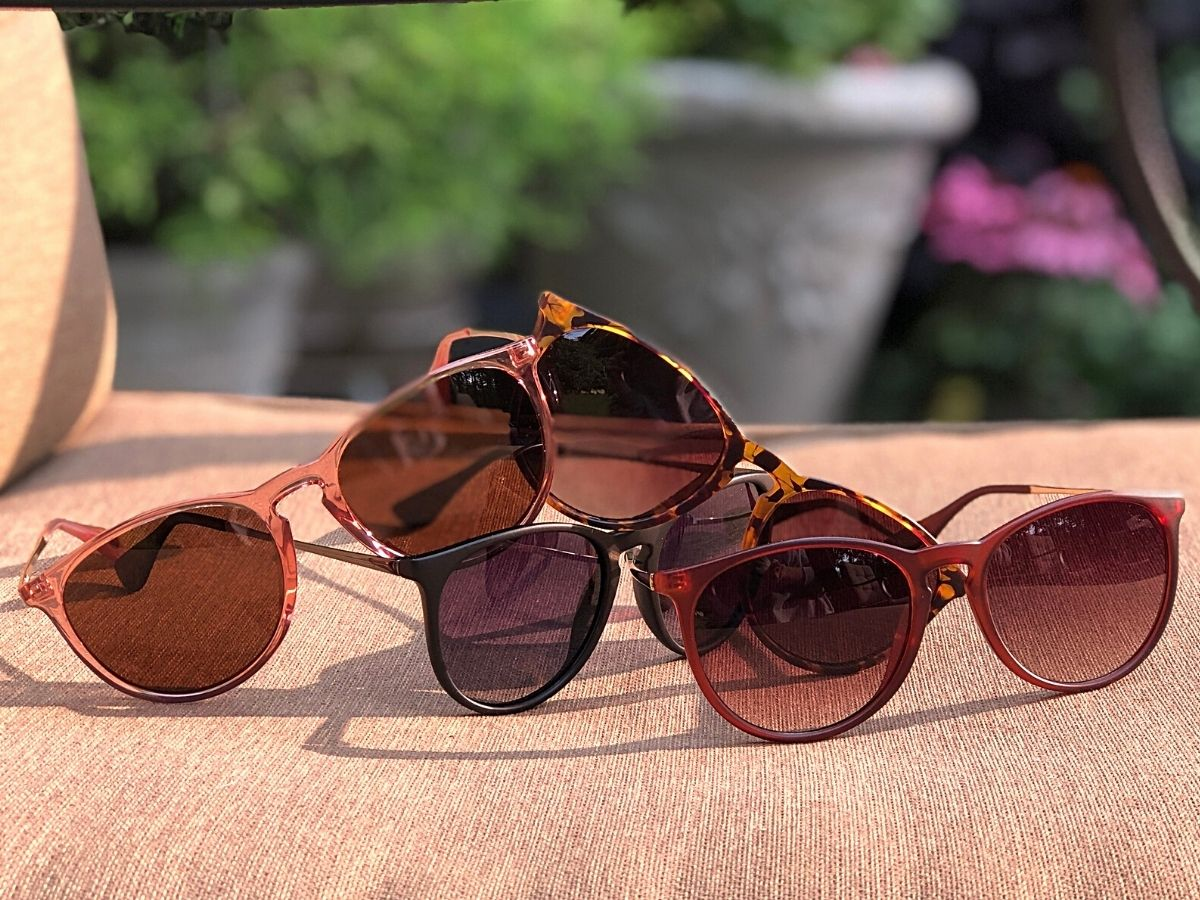four pairs of sunglasses resting on pink lounge chair