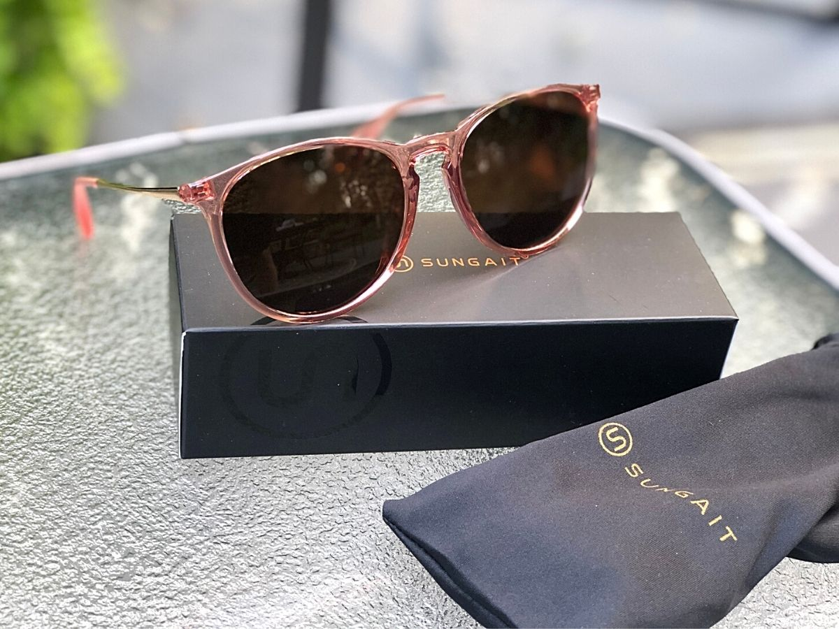 pink framed sunglasses resting on package with carrying bag next to package