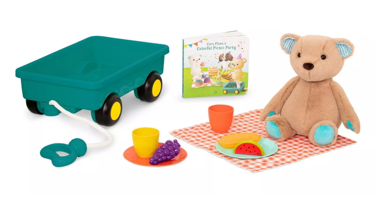 teddy bear on a picnic blanket with picnic items next to a book and a wagon