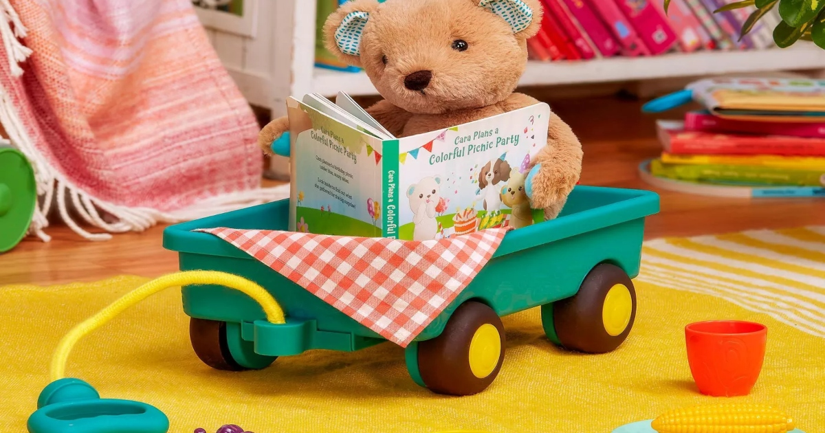 teddy bear in a plastic wagon reading a book with picnic items around it on the floor