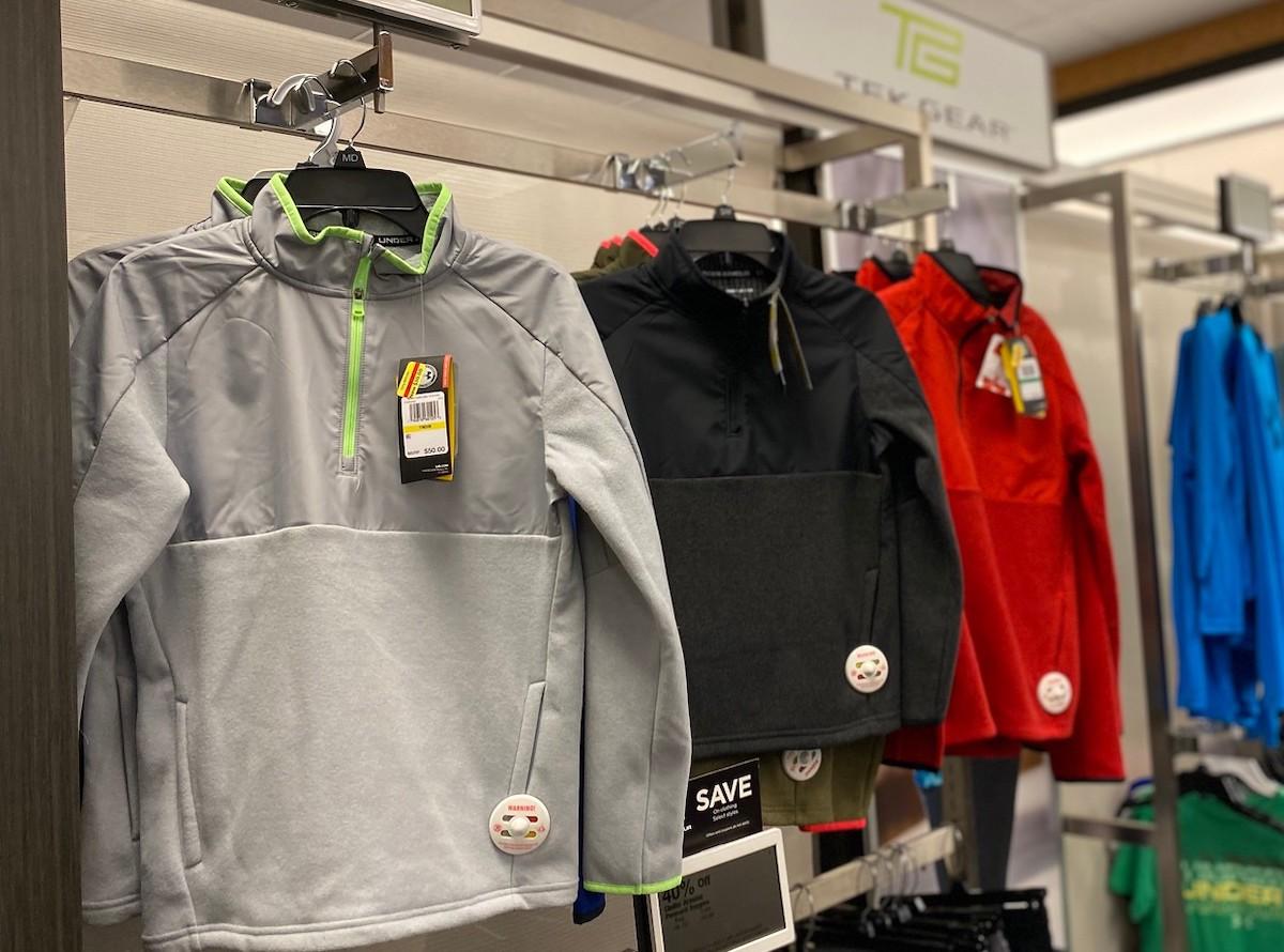 row of gray black red boys tek gear sweatshirts hanging up in store