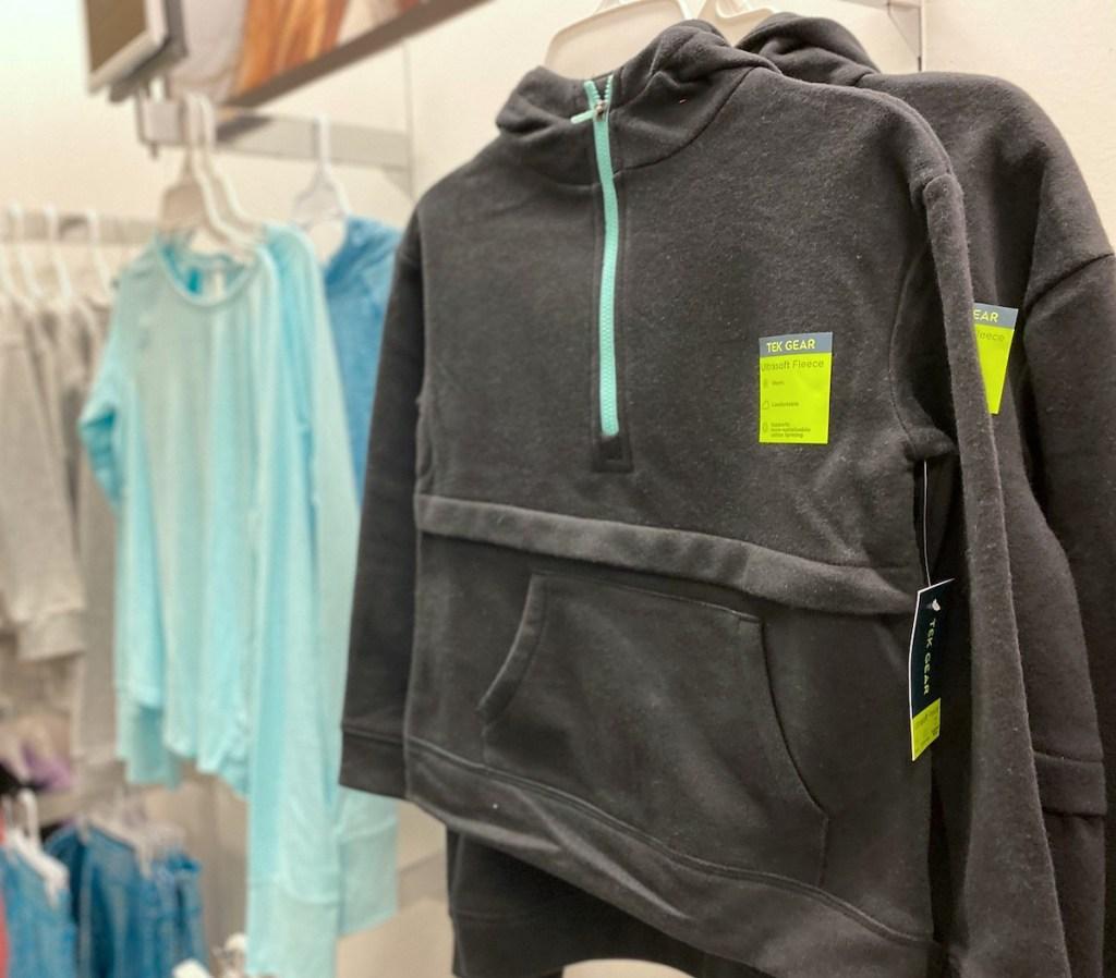 dark gray half zip sweatshirts hanging on store shelf