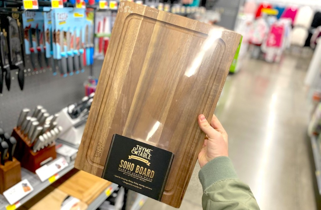 hand holding thyme and table wood cutting board in walmart store aisle
