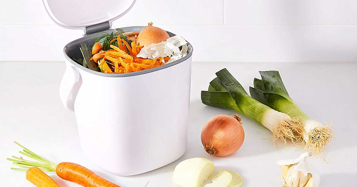 white compost bin on table with veggies
