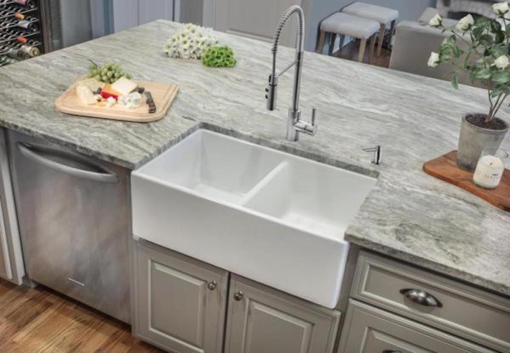 white farmhouse 50/50 split sink in home with grey counter tops