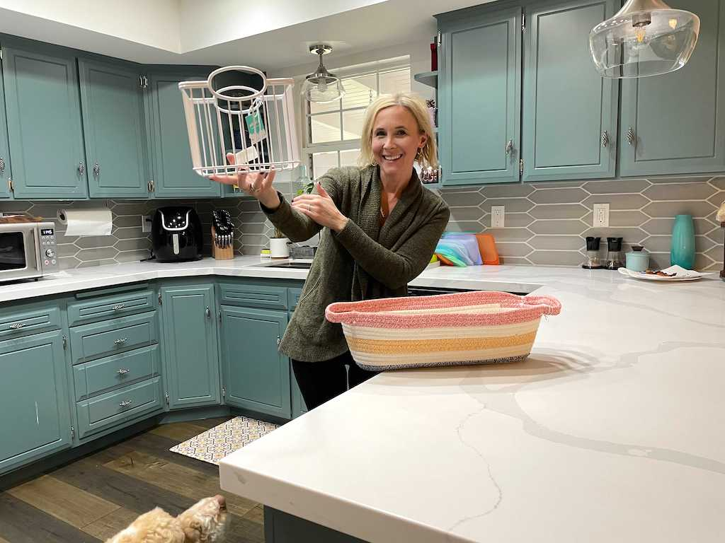 woman holding storage bin in kitchen