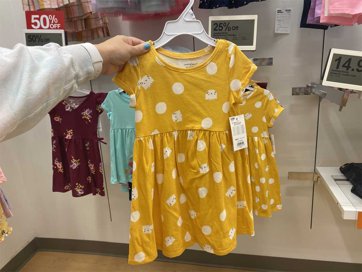 hand holding up a girls yellow dress in store