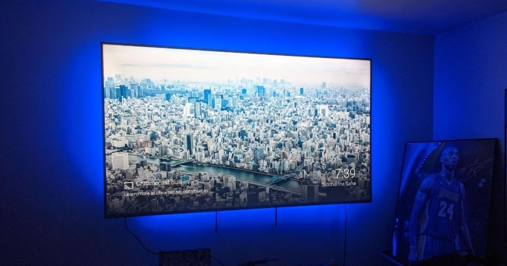 flat screen tv on wall with blue lights surrounding it