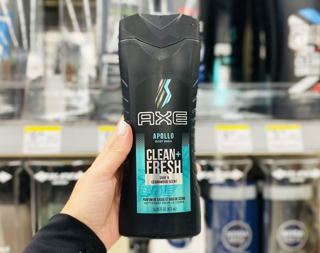 person holding up black bottle of axe body wash