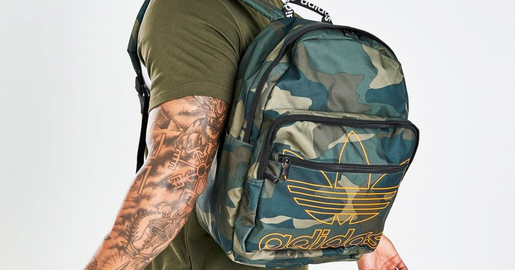 man with camo print adidas backpack on his back