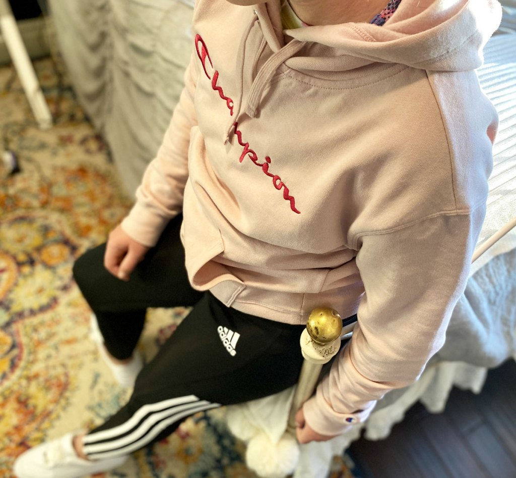 girl leaning against bed wearing pink champion hoodie and black adidas pants