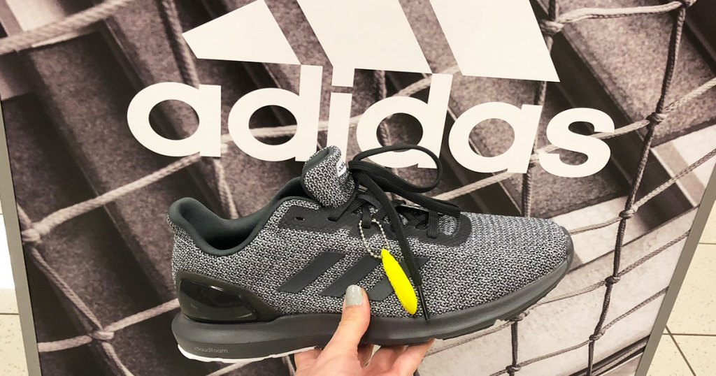 person holding a grey adidas shoe in front of adidas sign
