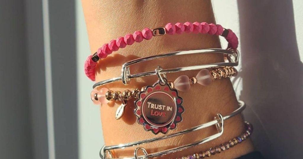 woman's wrist with severalAlex & Ani bangle bracelets