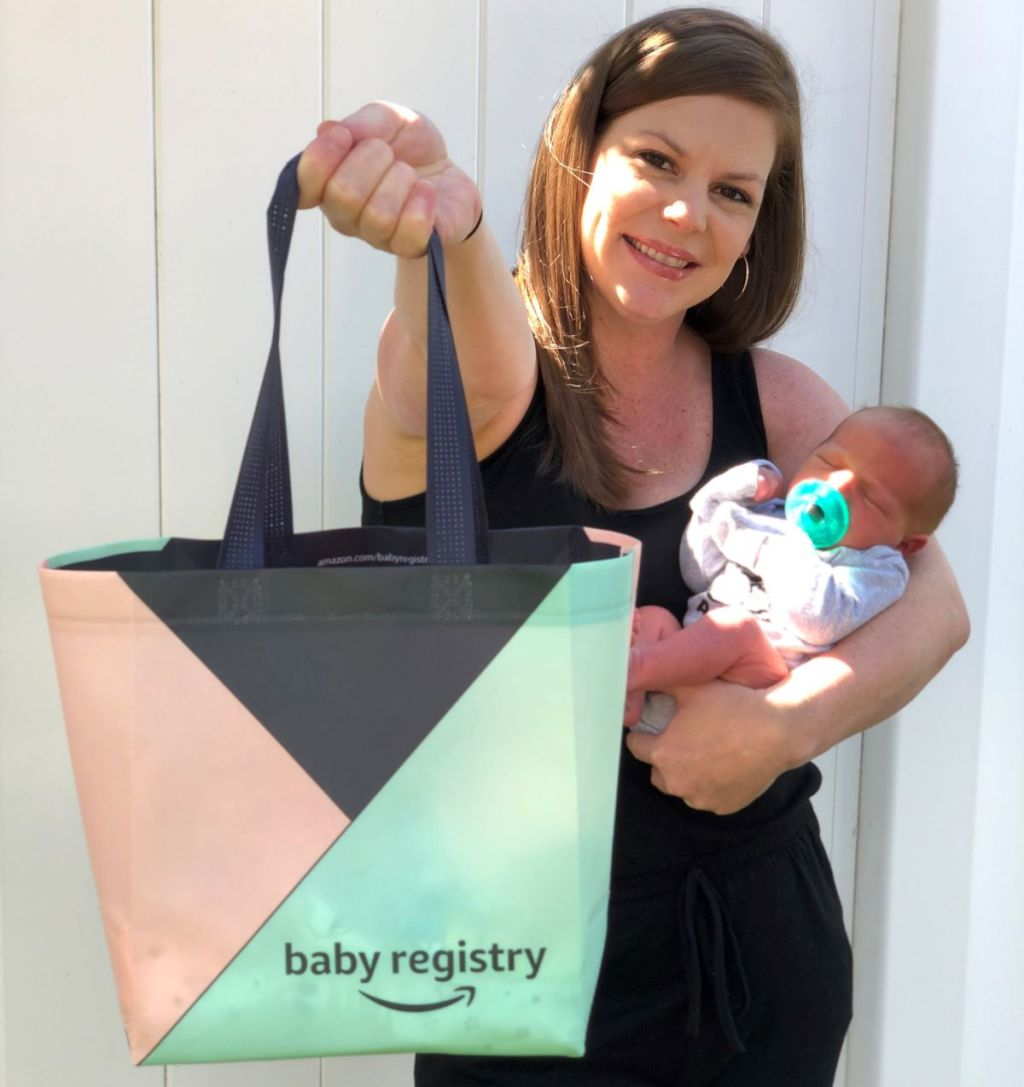 woman holding a baby and an Amazon Registry gift bag
