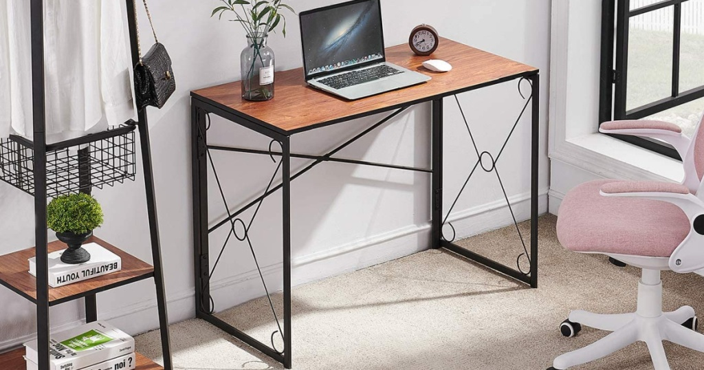 Small folding desk in an office area with a Macbook