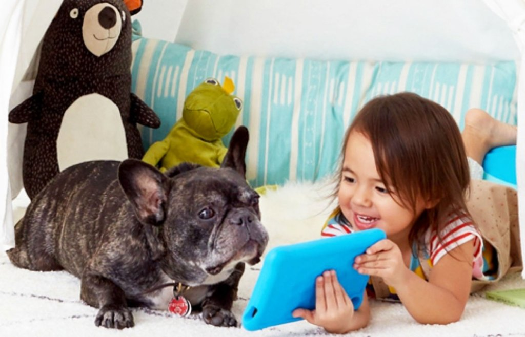 girl showing screen of tablet to dog laying next to her