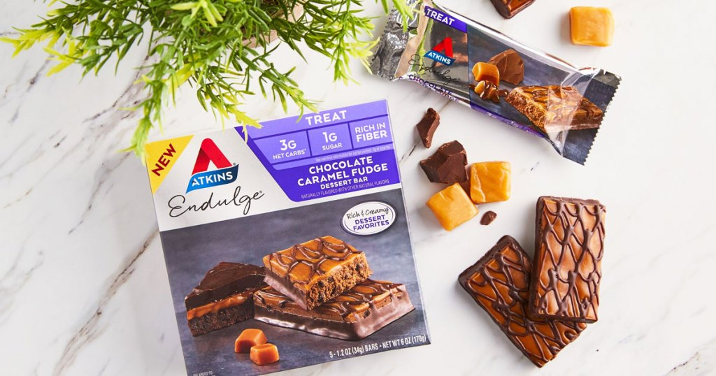 box of atkins chocolate caramel fudge bars with two unwrapped bars next to it