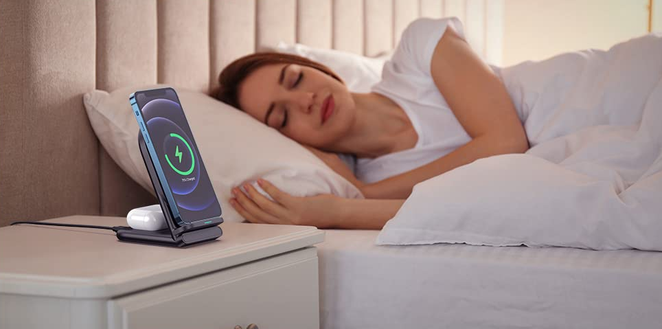 woman sleeping with a phone charger next to the bed
