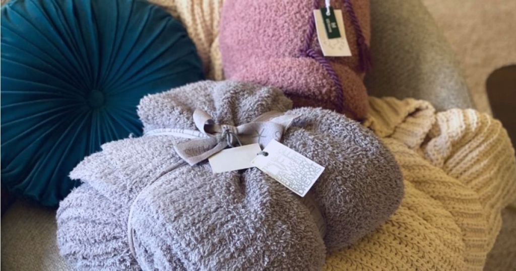 Barefoot Dreams blankets and pillows on a couch